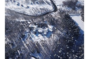 Aerial, Drone View of Snow Covered Evergreen Christmas Tree Forest and house after Snow