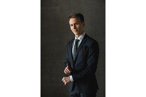 Handsome businessman in black formal suit on gray background
