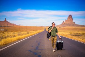 Young traveler with a suitcase walking on a road in Arizona