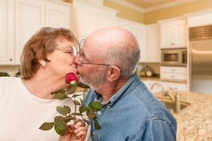 Senior Couple In Kitchen Kissing