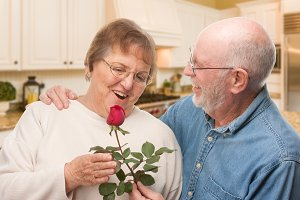 Senior Couple In House with Rose