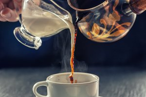 pouring cup of hot coffee and milk