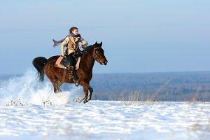 Winter horse riding on snowy field