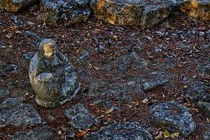Smiling Buddha among rocks