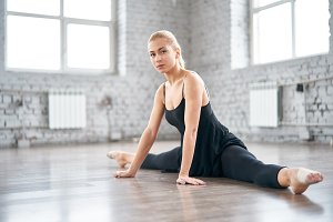 Charming slender female dancer doing the splits