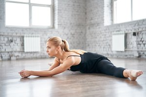 Charming slender female dancer doing the splits