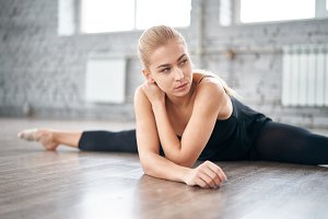 Slim thoughtful woman stretching her body in the gym