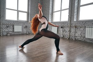 Young beautiful dancer posing on a studio background.