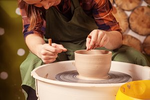 Potter sculpts a deep bowl