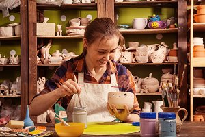Woman paints a gray clay bowl