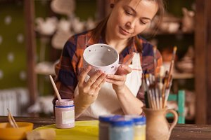 Potter paints a gray clay bowl