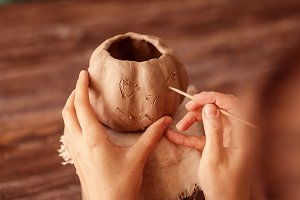 Artist painting clay pumpkin