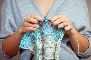 Woman knits  gray cardigan