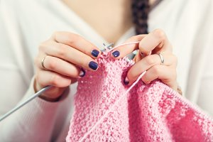Woman knits pink sweater