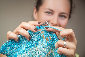 Woman knits blue sweater