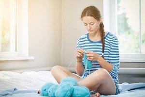 Brunette knits blue sweater