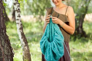Woman knits in a birch forest