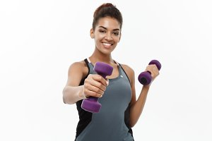 Healthy and Fitness concept - Beautiful American African lady in fitness clothes workout with dumbbell. Isolated on white background.