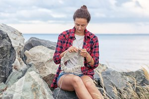 Woman  knits  near the sea