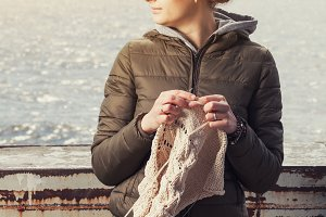 Woman knits near sea