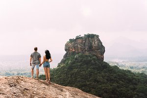 A couple in love stands on a rock