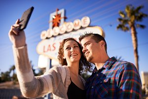 couple taking selfie by vegas sign
