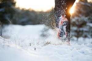 Image of running man in sneakers on snowy forest in winter
