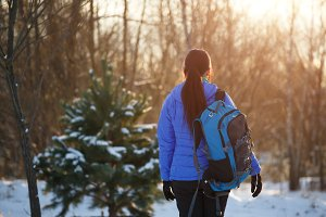 Photo from back of sports woman with backpack in winter forest