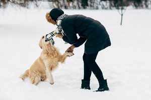 Picture of woman in black jacket with retriever walking in winter park