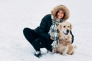 Photo of smiling woman with labrador in winter park