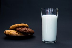 A glass of milk with ciikies.