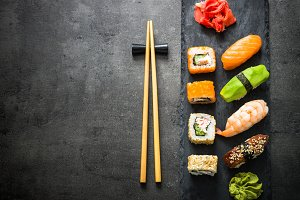 Sushi and sushi roll set on black stone table top view