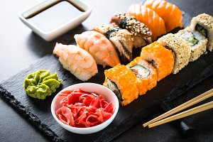 Sushi and sushi roll set on black stone table.
