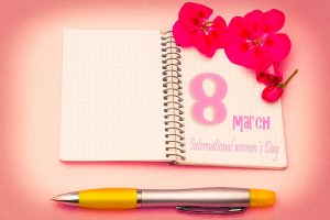 notebook with flowers and pen on pin