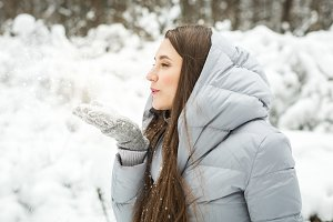 woman Blowing Snow in winter