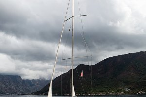 white large yacht stands at the pier in the town of Perast