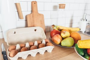 Cardboard egg box and vegetables on wooden table.
