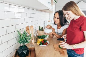 Two women in the kitchen prepare salad.