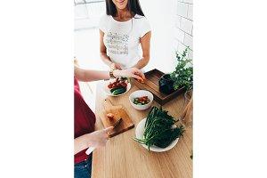 Two girls friends preparing dinner in kitchen cooking salad.