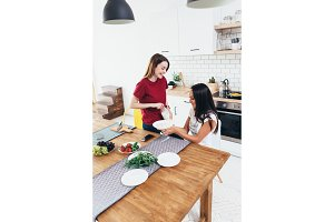 Woman with her friend eat in kitchen,