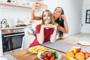 Women preparing food playing with vegetables in kitchen having fun and taking selfie.