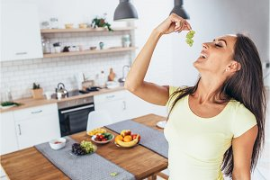 Beautiful playful woman eating grape in kitchen.