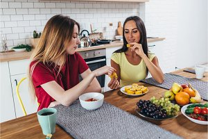 Two female friends having breakfast at table in kitchen.