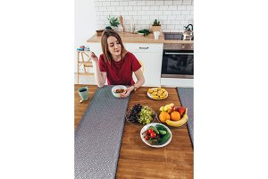 Woman at home eating fruits and vegetables top view.