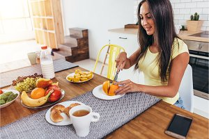 Woman in kitchen cut orange for breakfast
