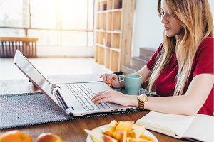 Woman in kitchen during her breakfast using her laptop