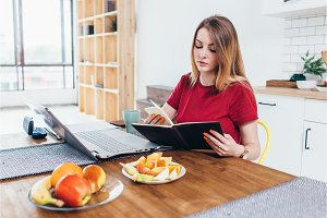 Woman sitting at working place in kitchen reading notes in notebook