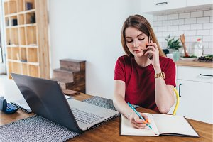 Woman working at home write notes while talking on phone