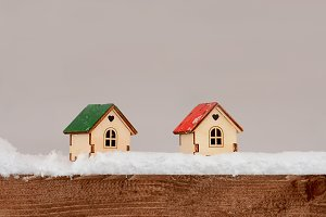 Two wooden small toy house with snow