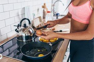 Fit girl breaks egg with knife Prepare omlet